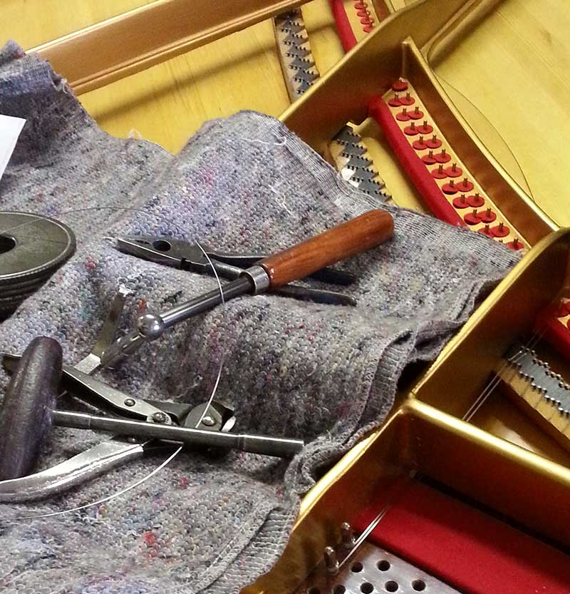 Piano restoration tools on grand piano